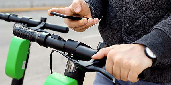Close shot of cyclist holding the bike's handlebar in one hand and a smartphone in the other.