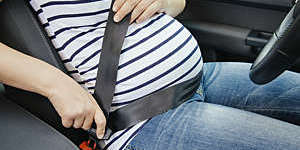 Close-up of pregnant woman buckling up in her car.