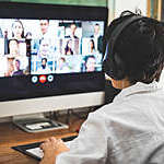 Back view of woman with headphones joining in a video conference from home.