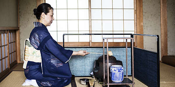 Kneeling Japanese woman in traditional kimono uses a Hishaku (bamboo ladle) during a tea ceremony.
