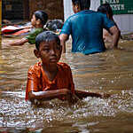 Indonesian children wade through flood waters on a street in Jakarta.