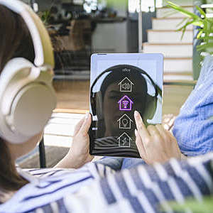 Young woman with tablet awith smart home control functions and headphones