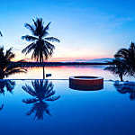 Palm trees reflecting in a luxury swimming pool with sunset views of the sea.
