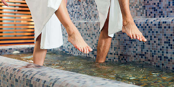 Close shot of a man and woman's feet as they tread through the water at a hydrotherapy centre.