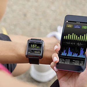 Close-up of woman's hand synchronizing her mobile phone with the smart watch heart-rate monitor on her wrist.