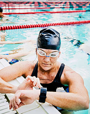 Female swimmer checks her fitness watch during exercise in an outdoor pool.