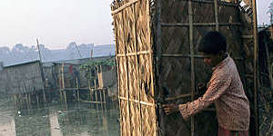 Third-world child tries to open the door of an outdoor toilet cubicle that is built on stilts over water