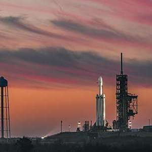 SpaceX launchpad against a red night sky.