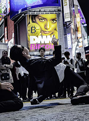 Japanese man performs a limbo dance on the street at Tokyo's Shibuya Crossing in front of a crowd of onlookers, with a big ad for Bitcoin in the background.