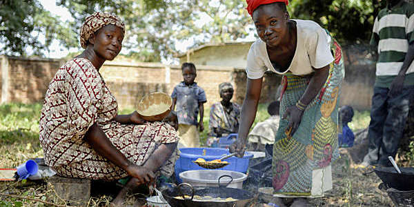 Two African women wearing traditional clothes and colorful headscarves prepare food on an outdoor open fire in Moundou, Chad.