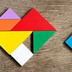 Colorful tangram puzzle in heart shape wait to fulfill on wood background (Concept of happy family, love fulfillment)