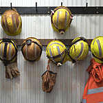 Row of yellow safety helmets hanging from a wooden rack at a mining site.