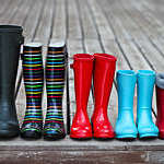 Front view of five pairs of colourful rain boots lined in a row.