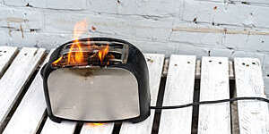Black and steel toaster with two slices of toast catches fire.