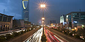 View of red and white light trails as cars stream up and down King Fahad Road in Riyadh, Saudi Arabia.
