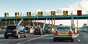 Cars queuing to go through a toll barrier.