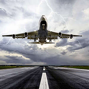 Low-angle shot of a passenger aircraft landing in extreme weather.