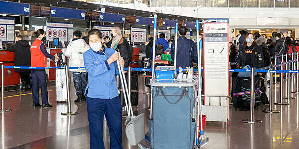 Masked woman in blue cleaning overalls takes a long-handled brush and dustpan from her trolley as passengers queue at the airport check-in area behind her.