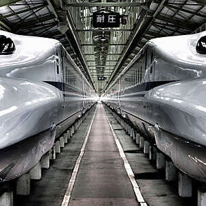 Vanishing perspective of two high-speed Japanese Shinkansen trains parked at a main station.