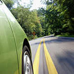 Close-up of green car speeding along a leafy road, captured with slight motion blur.