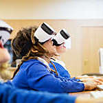 Young children, open-mouthed with excitement as they use virtual reality goggles in a computer lab at school.