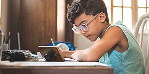 Side view of young boy using a tablet while doing his homework.