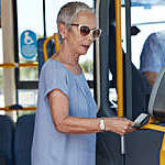 Mature woman using travel card to pay for public bus ride.