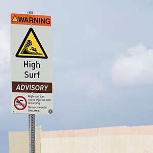 High surf wave warning sign the beach.