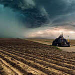 Tornado-chasing vehicle with IMAX camera drives along ploughed fields towards a looming storm in Colorado, USA