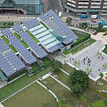 Aerial view of long strips of solar panels on the roof of a building.
