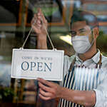 Close-up of a young man with face mask hanging an open sign on the door of a grocery store.