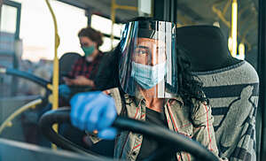 Female bus driver wears a protective transparent face shield during the COVID-19 pandemic.