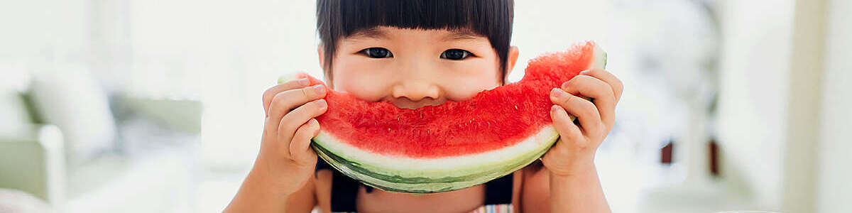 Asian little girl eating a slice of watermelon at home.