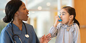 Female doctor playfully teaches a small asthmatic girl to use an inhaler.