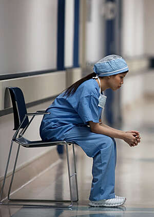 Female healthcare worker dressed in blue uniform sits on a chair lost in thought.