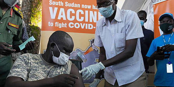 Military general, seated, receives the COVID-19 vaccine from a healthcare professional at the Juba military hospital in South Sudan.