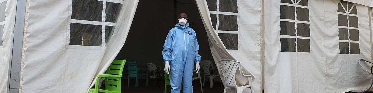 Doctor in blue overalls, gloves and mask stands at the entrance of a tent health centre in Djibouti