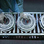 Overhead view of worker's hands moving clutch pressure plates down the production line in an industrial clutch factory.