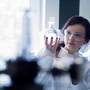 Female biochemistry scientist in lab coat and protective glasses holds up a round flask to study its content.