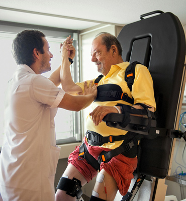 An elderly man is doing exercise with the help of a care taker