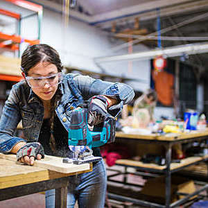 Female carpenter cutting wood using a power saw in a workshop. Los Angeles, October 2016